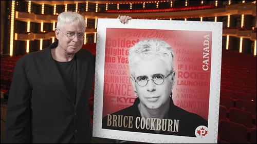 Bruce Cockburn poses with his forthcoming stamp, which will be issued June 30