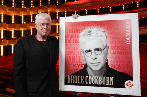Bruce Cockburn at the National Art Centre in Ottawa with his stamp image.